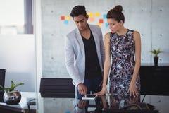 Hombre de negocios joven usando la tableta digital mientras que se coloca con el colega femenino Fotos de archivo