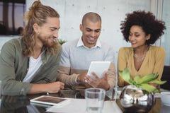 Hombre de negocios joven usando la tableta digital mientras que se sienta con los colegas Fotografía de archivo libre de regalías