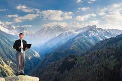 Hombre de negocios joven usando su ordenador portátil en el top de la montaña Fotografía de archivo