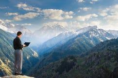 Hombre de negocios joven usando su ordenador portátil en el top de la montaña Fotos de archivo libres de regalías