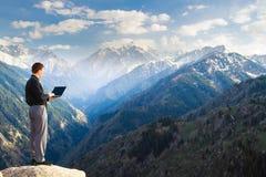 Hombre de negocios joven usando su ordenador portátil en el top de la montaña Imagen de archivo
