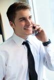 Hombre de negocios joven usando su teléfono móvil en oficina Imagen de archivo libre de regalías
