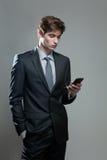 Hombre de negocios joven usando un teléfono móvil Fotos de archivo libres de regalías
