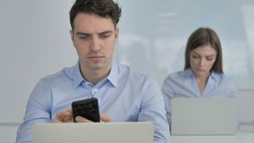 Hombre de negocios joven Using Smartphone en el trabajo metrajes