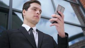 Hombre de negocios joven Using Smartphone, envío de mensajes de texto almacen de metraje de vídeo