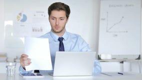 Hombre de negocios joven Working en el contrato, papeleo almacen de video