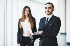 Hombre de negocios joven y confiado con el ordenador portátil que se coloca delante de mujer de negocios imagen de archivo