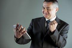 Hombre de negocios jubiloso que anima un éxito foto de archivo