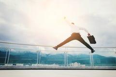 Hombre de negocios Jump en un tejado y mirada de concepto del éxito de la ciudad Fotografía de archivo libre de regalías