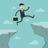 Hombre de negocios Jumping a través del abismo Imágenes de archivo libres de regalías