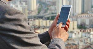 hombre de negocios 4k que usa un smartphone contra fondo urbano moderno del edificio almacen de metraje de vídeo