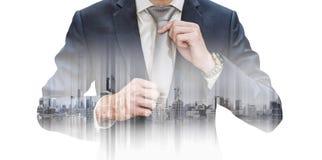 Hombre de negocios de la exposición doble que ata la corbata y los edificios, aislados en el fondo blanco Fotos de archivo libres de regalías