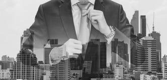 Hombre de negocios de la exposición doble que lleva a cabo la corbata con los edificios modernos en el fondo de la ciudad de Bang fotos de archivo