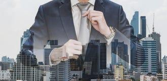 Hombre de negocios de la exposición doble que lleva a cabo la corbata con los edificios modernos en fondo de la ciudad de Bangkok imagenes de archivo
