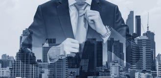 Hombre de negocios de la exposición doble que lleva a cabo la corbata con los edificios modernos en fondo de la ciudad de Bangkok Imagen de archivo