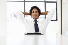 Hombre de negocios With Laptop Sitting en el escritorio en el pensamiento de la oficina Foto de archivo libre de regalías