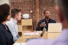 Hombre de negocios Leading Office Meeting alrededor de la tabla imágenes de archivo libres de regalías