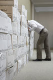 Hombre de negocios Leaning Over Boxes en trastero foto de archivo libre de regalías