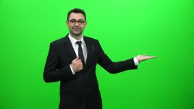 Hombre de negocios Lifting Or Presenting algo en la pantalla verde Lado izquierdo almacen de metraje de vídeo