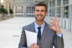 Hombre de negocios lindo que guiña y que da una muestra ACEPTABLE Foto de archivo libre de regalías