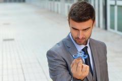 Hombre de negocios lindo que juega con un hilandero de la mano imagen de archivo