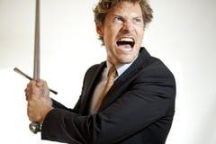 Hombre de negocios loco que ataca con una espada Imagen de archivo libre de regalías