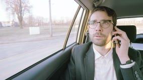 Hombre de negocios Looking Around y terminación de una llamada de teléfono almacen de video