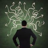 Hombre de negocios Looking At Arrows Imagen de archivo libre de regalías