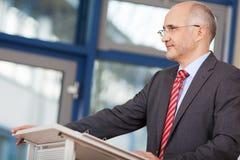Hombre de negocios Looking Away While que se coloca en el podio Fotos de archivo libres de regalías
