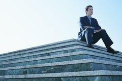 Hombre de negocios Looking Away While que se sienta en la escalera de mármol Imagen de archivo