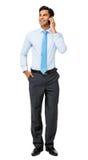 Hombre de negocios Looking Away While que usa el teléfono elegante Imágenes de archivo libres de regalías