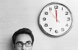 Hombre de negocios Looking At Clock en la pared en oficina fotos de archivo libres de regalías