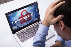 Hombre de negocios Looking At Laptop con la palabra de Ramsomware en la pantalla imagenes de archivo