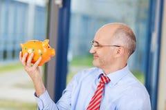 Hombre de negocios Looking At Piggybank en oficina Imagen de archivo