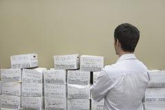 Hombre de negocios Looking At Stack de las cajas de la limadura imagenes de archivo