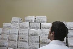 Hombre de negocios Looking At Stack de las cajas de la limadura fotos de archivo