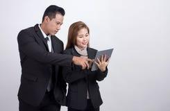 Hombre de negocios de los asiáticos y empresaria del consejero que discute y que trabaja así como la tableta digital en el fondo  imagen de archivo