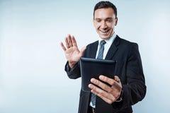 Hombre de negocios maduro alegre en el traje que tiene llamada video fotografía de archivo libre de regalías