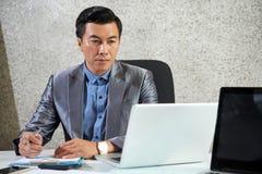 Hombre de negocios maduro asiático que trabaja en el ordenador portátil en la oficina fotos de archivo