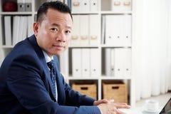 Hombre de negocios maduro asiático que trabaja en la oficina fotografía de archivo libre de regalías