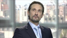 Hombre de negocios maduro atractivo con la expresión pensativa metrajes