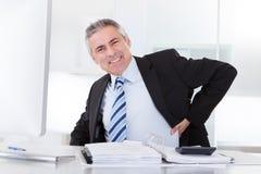 Hombre de negocios maduro con dolor de espalda Foto de archivo libre de regalías
