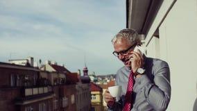 Hombre de negocios maduro con el smartphone que se coloca en una terraza en la ciudad, haciendo una llamada de teléfono almacen de video