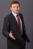 Hombre de negocios maduro confiado que se coloca delante de un backgro gris Fotografía de archivo