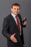 Hombre de negocios maduro confiado que se coloca delante de un backgro gris Imagen de archivo libre de regalías