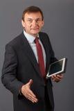Hombre de negocios maduro confiado que se coloca delante de un backgro gris Fotos de archivo