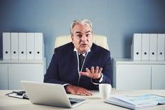 Hombre de negocios maduro emocional que muestra gesto el tranquilizar foto de archivo libre de regalías
