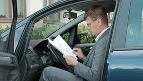 Hombre de negocios maduro en el funcionamiento del coche Hojee los documentos almacen de metraje de vídeo