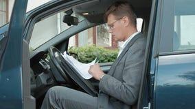 Hombre de negocios maduro en el funcionamiento del coche Hojee los documentos almacen de video