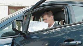 Hombre de negocios maduro en el funcionamiento del coche Hojee los documentos metrajes